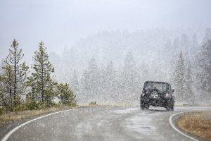 ein fahrendes Auto auf kurviger Straße im Schnee